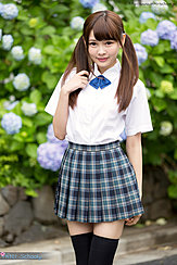 Student In Uniform Playing With Her Pigtails Wearing Pleated Skirt