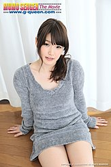 Yuna Ishihara Sitting On Wood Flor Hands Down Beside Her Long Hair In Ponytail Over Her Shoulder Wearing Grey Sweater