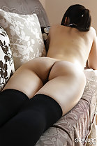 Lying on her front on couch naked back bare ass black stockings