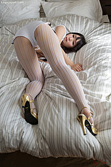 Sakura Sena With Her Ass Raised On Bed Looking Over Her Shoulder In Tight Shorts Wearing Pantyhose In Gold High Heels