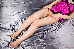 Lying On Her Back In Pink Lingerie Riding Up Over Her Shaved Pussy Pussy Cleft Between Her Thighs Hands Resting On Her Legs Bare Feet