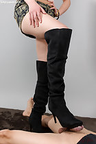 Hand resting on thigh in short skirt rubbing his cock with the sole of her black boots