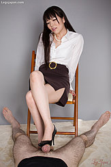 Sitting On Chair With Her Legs Crossed Long Hair Pearl Necklace Visible At Open Neckline Rubbing Cock With Sole Of Her High Heels