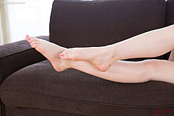 Stretching Out Her Bare Feet On Sofa