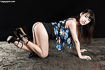 On all fours looking to the side long hair hanging down short skirt raised wearing high heels