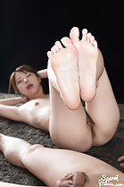 On her back nude raising her bare feet cum on her feet