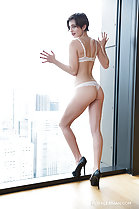 Pressed against window hands raised wearing bra and panties in high heels